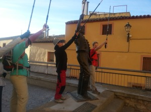 Pilgrims assisting the statue to shoo away the storks