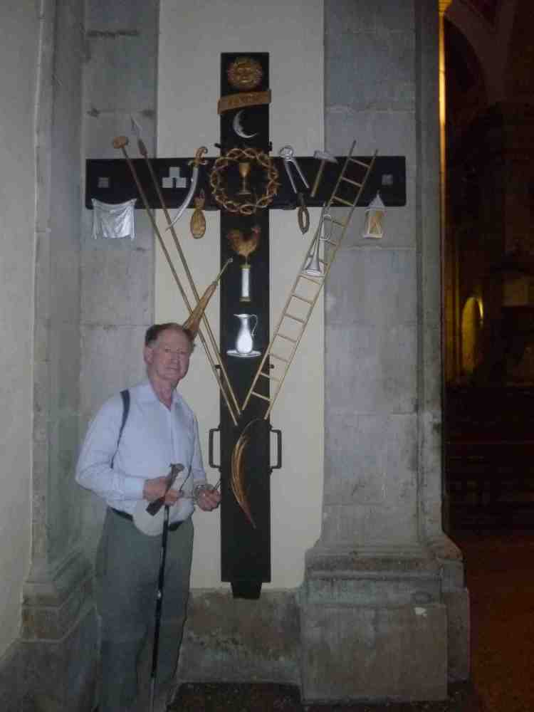 Fr John Fitzgerald standing by a cross in the church at Tarrega which has various symbols of the crucifixion
